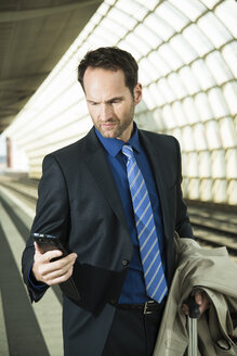 Businessman at train station looking at cell phone - UUF000366