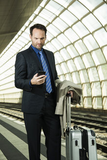 Businessman at train station looking at cell phone - UUF000367