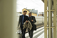 Two businessmen talking at train station - UUF000455