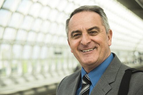 Portrait of confident senior businessman at train station - UUF000374