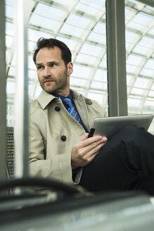 Businessman at train station using digital tablet - UUF000378
