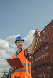 Man with clipboard wearing reflective vest at container port - UUF000412