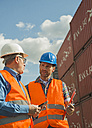 Two men with safety helmets and reflective vests talking at container port - UUF000414