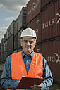 Man with clipboard wearing reflective vest at container port - UUF000419