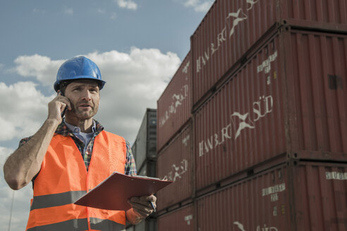 Man with clipboard on the phone at container port - UUF000421