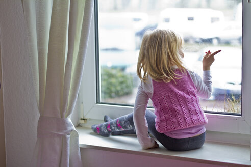Little girl sitting on window sill looking out of window - JFEF000404