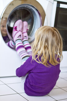 Little girl watching washing machine - JFEF000408