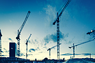 Germany, Bavaria, Munich, Cranes against blue sky - FC000151