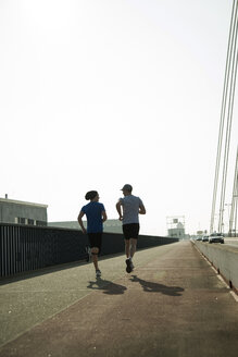 Young man and teenager running on bridge - UUF000399