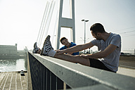 Young man and teenager stretching on bridge - UUF000401