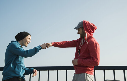 Young man and teenager at railing under blue sky - UUF000404