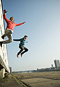 Young man and teenager jumping mid air - UUF000442