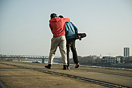 Young man and teenager with skateboard hugging - UUF000449
