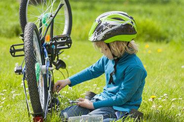 Little boy repairing bicycle on meadow - MJF001084