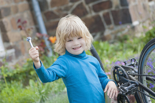 Portrait of smiling little boy with tool for repairing bicycle - MJF001089