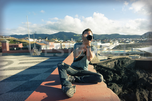 Portugal, Azores, Sao Miguel, Man on wall taking picture - ONF000541