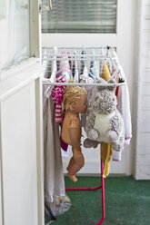 Clothes, doll and stuffed animal drying on clotheshorse at balcony - JFEF000393