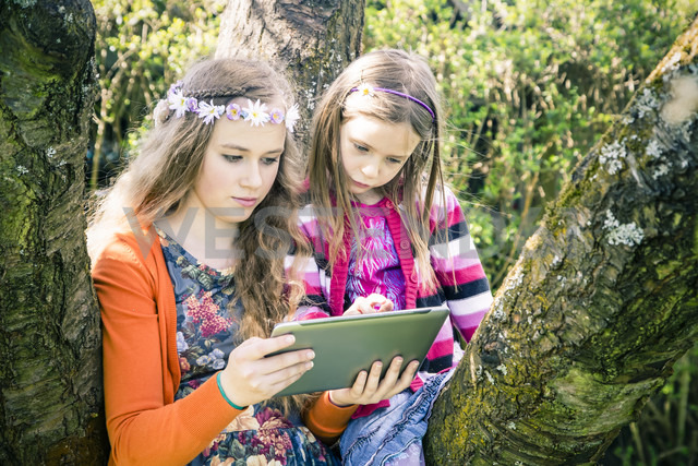 Two sisters with tablet computer together in garden - SARF000571