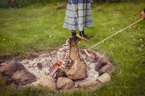 Girl grilling sausage at camp fire in the garden, partial view - MJF001158