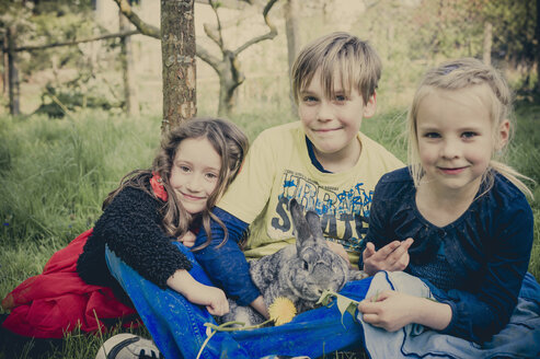 Three children with rabbit sitting on a meadow - MJF001109
