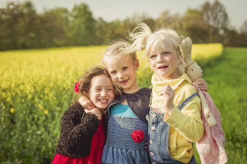 Three little girls standing in front of rape field - MJF001110