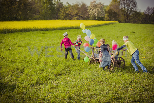 Six children on the move with wooden trolley and balloons - MJF001113 - Jana Mänz/Westend61