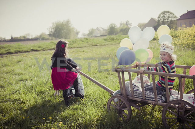 Three children on the move with wooden trolley and balloons - MJF001115 - Jana Mänz/Westend61