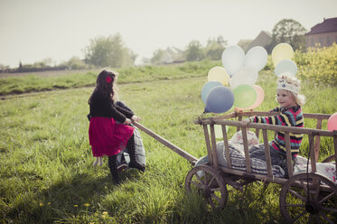 Three children on the move with wooden trolley and balloons - MJF001115