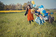 Three children on the move with wooden trolley and balloons - MJF001117