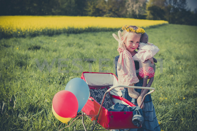 Smiling little girl holding doll and soft toy standing on meadow with doll carriage - MJF001119