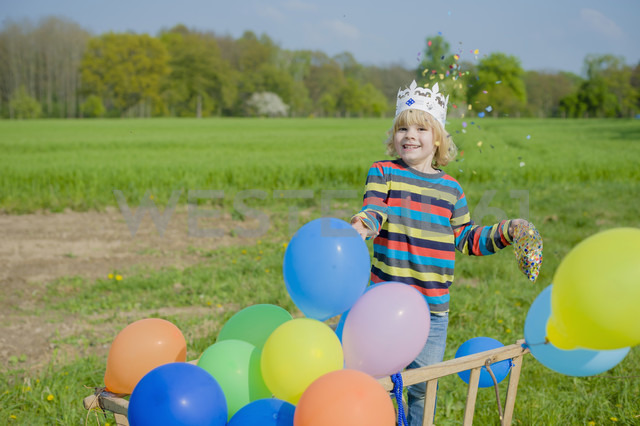 Smiling little boy throwing confetti - MJF001134