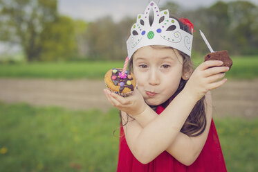 Portrait of little girl with birthday muffins making face - MJF001135