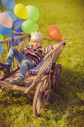 Little boy lying on wooden trolley holding balloons - MJF001145