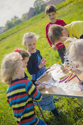 Children painting paper crowns for birthday party - MJF001147