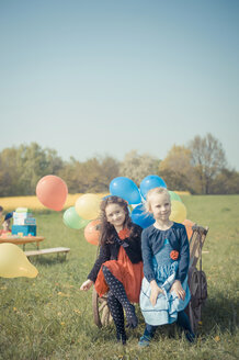 Two little girls sitting on wooden trolley with balloons - MJF001154
