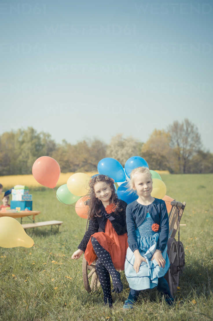 Two little girls sitting on wooden trolley with balloons - MJF001154 - Jana Mänz/Westend61