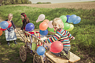 Three children on the move with wooden trolley and balloons - MJF001155