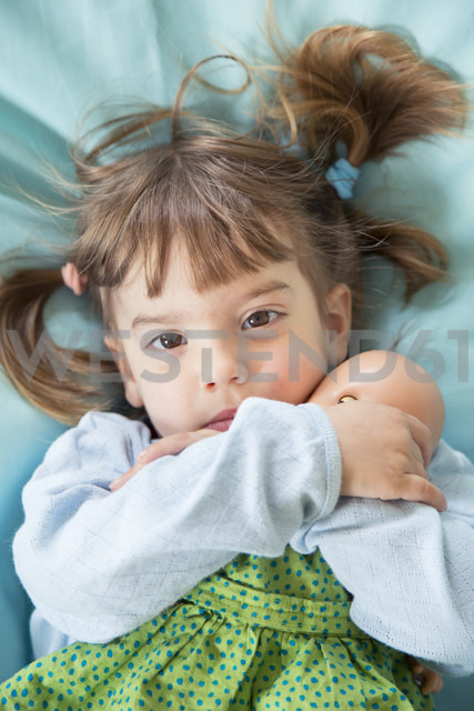 Portrait of little girlwith doll  lying on bean bag, elevated view - LVF001167