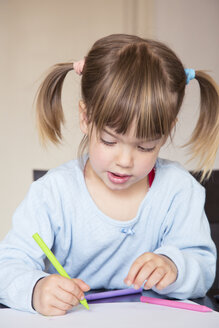 Portrait of little girl painting with wax crayons - LVF001164
