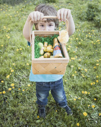 Little boy showing his basket with chocolate Easter bunnies - ZMF000270