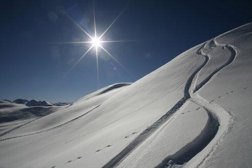 Austria, Kitzbuehel, snow with ski tracks against the sun - TMF000015