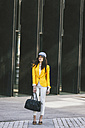 Spain,Catalunya, Barcelona, young modern woman with yellow jacket on the move - EBSF000218