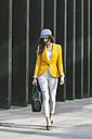 Spain,Catalunya, Barcelona, young modern woman with yellow jacket on the move - EBSF000201