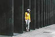 Spain,Catalunya, Barcelona, young modern woman with yellow jacket on the move - EBSF000200