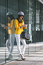 Spain,Catalunya, Barcelona, young modern woman with yellow jacket leaning against glass facade - EBSF000216