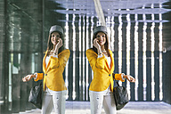 Spain,Catalunya, Barcelona, smiling young woman with yellow jacket reflecting in glass facade - EBSF000197