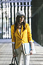 Spain,Catalunya, Barcelona, young modern businesswoman with yellow jacket on the move - EBSF000213