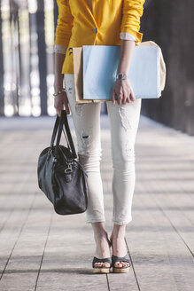 Spain,Catalunya, Barcelona, young modern businesswoman with yellow jacket on the move, partial view - EBSF000203