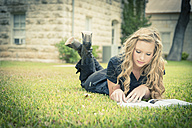 Portrait of young woman lying on grass reading a book - ABAF001342