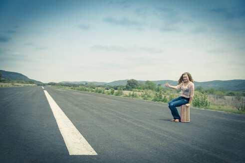 Young woman hitchhiking at empty street - ABAF001338